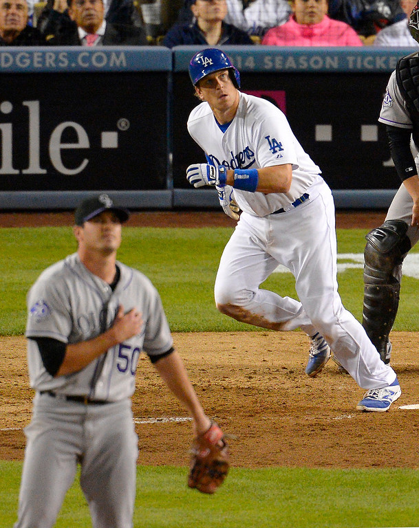. Los Angeles Dodgers\' A.J. Ellis, right, hits a two-run home run as Colorado Rockies starting pitcher Jeff Manship looks on during the fifth inning of their baseball game, Friday, Sept. 27, 2013, in Los Angeles.  (AP Photo/Mark J. Terrill)