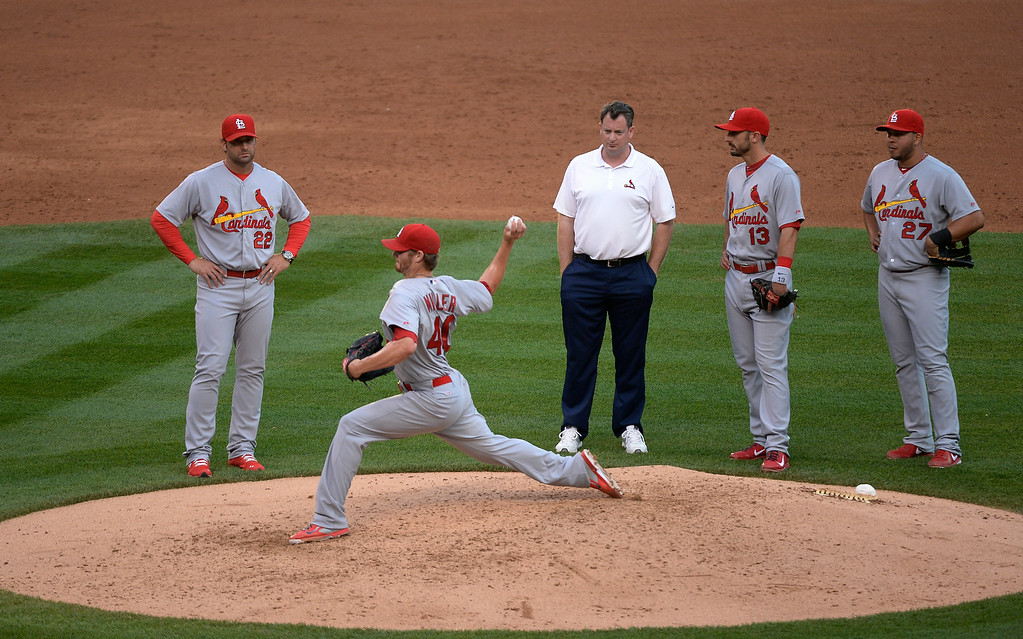 . DENVER, CO - JUNE 24: St. Louis Cardinals starting pitcher Shelby Miller (40) throws a pitch during a break in the action as the trainer looks on June 24, 2014 at Coors Field. Miller left the game with stiffness in his back in the third inning. (Photo by John Leyba/The Denver Post)