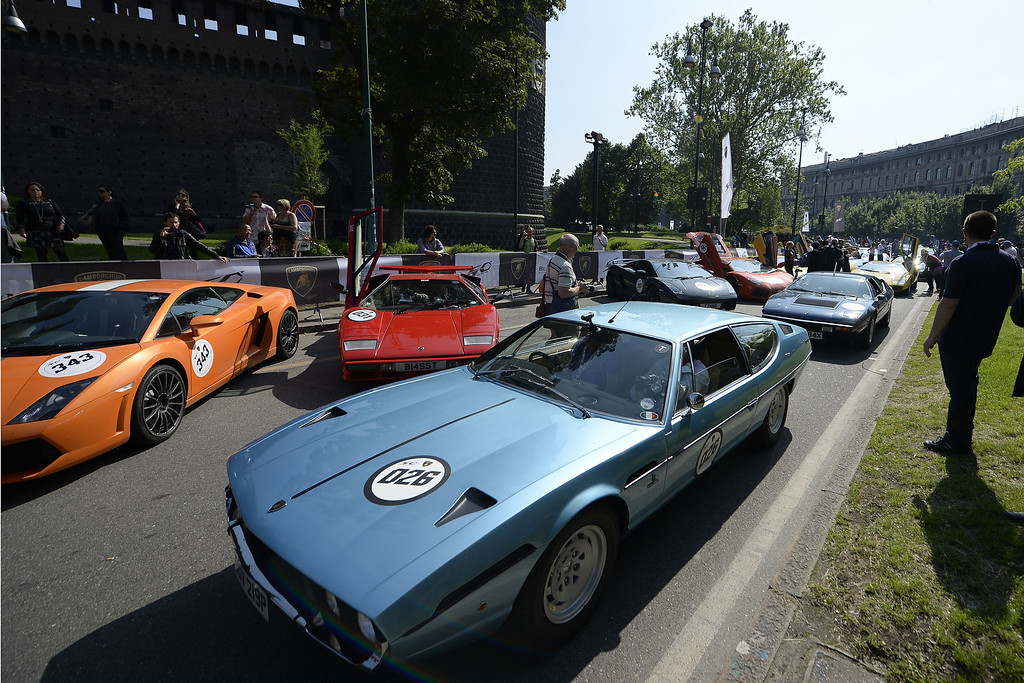 . People look at Lamborghini cars on May 8, 2013 in Milan. Two hundred and fifty vintage and modern Lamborghini cars will parade through Italian cities, starting from downtown Milan, to celebrate the 50th anniversary of the brand. AFP PHOTO / OLIVIER MORIN/AFP/Getty Images