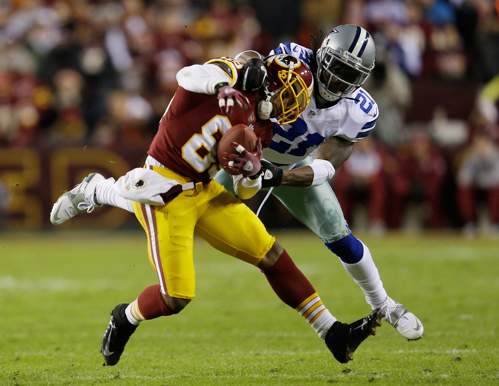 . LANDOVER, MD - DECEMBER 30:  Santana Moss #89 of the Washington Redskins is tackled  by Mike Jenkins #21 of the Dallas Cowboys after catching a pass in the first quarter at FedExField on December 30, 2012 in Landover, Maryland.  (Photo by Rob Carr/Getty Images)