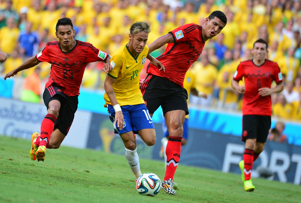 . Brazil\'s forward Neymar (C) controls the ball between Mexico\'s midfielder Jose Vazquez (L) and Mexico\'s defender Francisco Rodriguez (R) during a Group A football match between Brazil and Mexico in the Castelao Stadium in Fortaleza during the 2014 FIFA World Cup on June 17, 2014. YURI CORTEZ/AFP/Getty Images