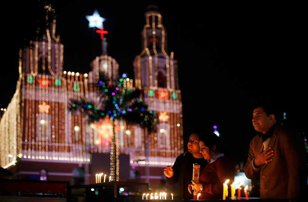 . Indian Christian people light candles and pray at the illuminated Sacred Heartís Cathedral on Christmas Eve in New Delhi, India, Tuesday, Dec. 24, 2013. Though Hindus and Muslims comprise the majority of the population in India, Christmas is celebrated with much fanfare. (AP Photo/Altaf Qadri)