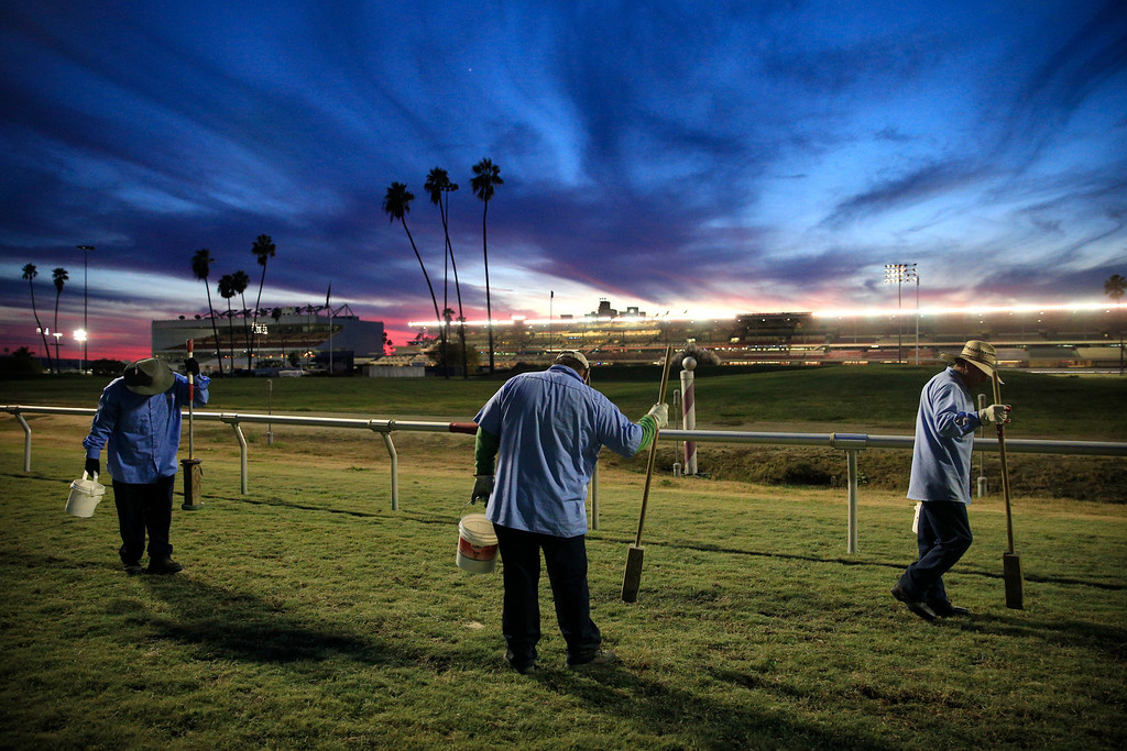 . Albert Razo, left, Rafael Chaidez, center, and Juan Renterea tamp holes left by horses after a race at Betfair Hollywood Park on Sunday, Dec. 15, 2013, in Inglewood, Calif. After 75 years of thoroughbred racing, Betfair Hollywood Park is closing for good. The 260-acre track that hosted Seabiscuit and the first Breeders\' Cup in 1984 will be turned into a housing and retail development starting next year. (AP Photo/Jae C. Hong)