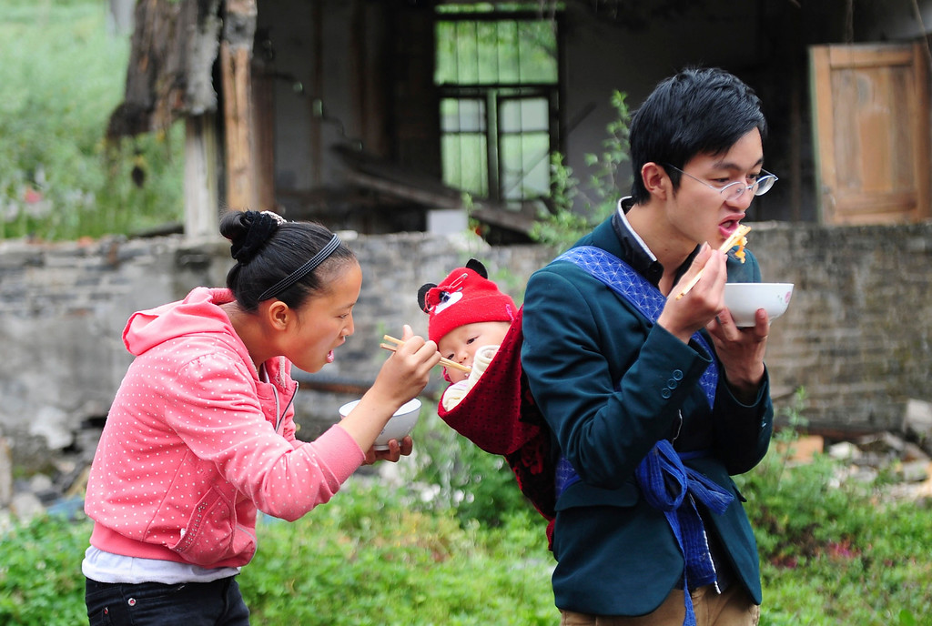 . A mother feeds her child, who is being carried by the father, after last Saturday\'s earthquake hit Lushan county, Ya\'an, Sichuan province, April 24, 2013. China has poured resources into Sichuan since the magnitude 6.6 quake hit early on Saturday, including 1 billion yuan ($161.9 million) for disaster relief and compensation. But mountainous terrain and poor infrastructure have made reaching victims difficult. The earthquake has left 196 dead, 21 missing and 11,470 injured, according to Xinhua News Agency. Picture taken April 24, 2013. REUTERS/Stringer