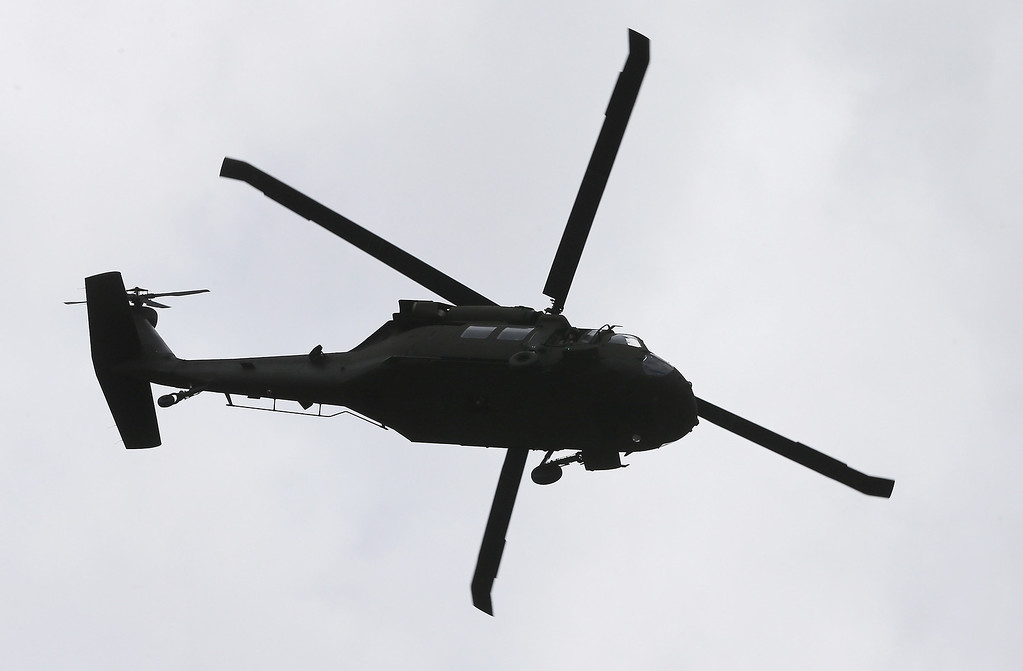 . A U.S. military helicopter flies above Watertown Mall as law enforcement agencies search for 19-year-old bombing suspect Dzhokhar A. Tsarnaev on April 19, 2013 in Watertown, Massachusetts.  (Photo by Mario Tama/Getty Images)
