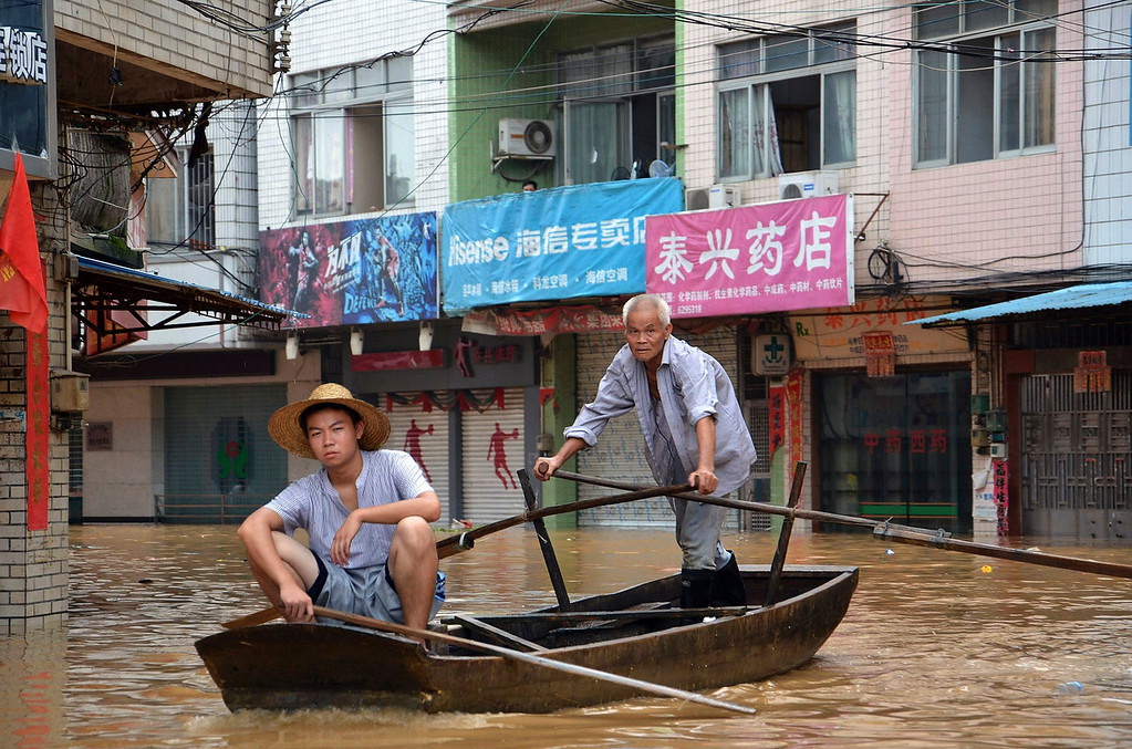 . Residents paddle a boat in flood waters triggered by torrential rains from typhoon Utor on a street in Fengkai in south China\'s Guangdong province Sunday, Aug. 18, 2013. Rains brought by last week\'s Typhoon Utor have caused severe flooding across Guangxi and neighboring Guangdong province. (AP Photo)