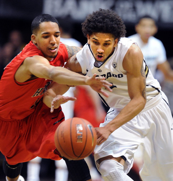 . Yolonzo Moore, left, of Hartford, and Askia Booker of CU, chase down a loose ball during the first half of the December 29, 2012 game in Boulder. (Cliff Grassmick / Daily Camera) December 29, 2012