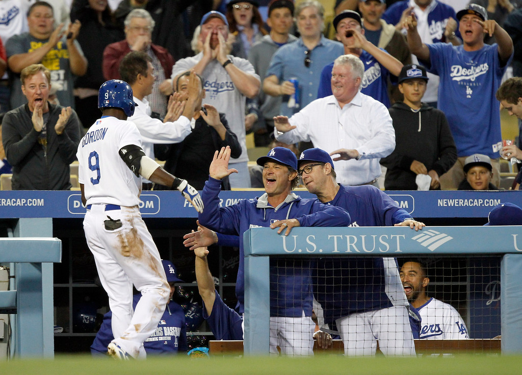 . Los Angeles Dodgers manager Don Mattingly, center, and  bench coach Tim Wallach, right, congratulate Dee Gordon (9) for scoring on a triple and an error by Colorado Rockies left fielder Charlie Blackmon, in the third inning of a baseball game on Monday, June 16, 2014, in Los Angeles.   (AP Photo/Alex Gallardo)