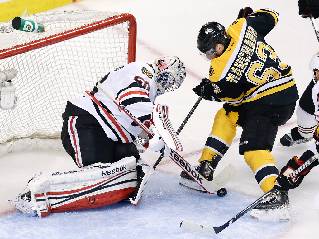 . Chicago Blackhawks goalie Corey Crawford (50) pokes the puck away from Boston Bruins left wing Brad Marchand (63) during the second period in Game 6 of the NHL hockey Stanley Cup Finals, Monday, June 24, 2013, in Boston. (AP Photo/Charles Krupa)