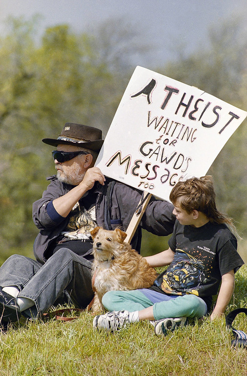 . Max Bell of Prescott Valley, Arizona, sits with his son Alex and dog Bandit on a hillside near the Branch Davidian compound in Waco, Texas on Saturday, March 27, 1993. The month-long standoff between David Koresh and his followers and federal agents has cost taxpayers more than $5 million so far. (AP Photo/George Widman)