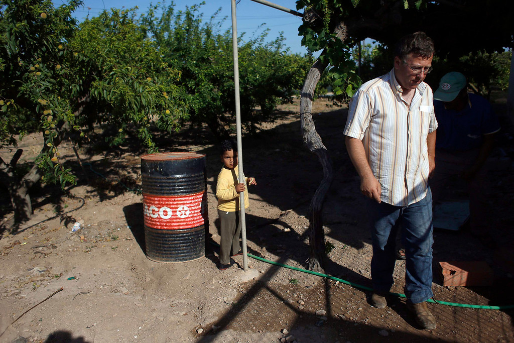 . Farmer Santiago Perez (R) walks away, as farm worker Mustapha El-Mezroui\'s three-year-old son Bilal looks on, at his farm house outside La Puebla, in the southern Spanish region of Murcia June 5, 2013.  El-Mezroui left his native Morocco for Spain on a makeshift boat in the mid-1990s, and now works as a keeper and farm hand on a farm outside La Puebla, Cartagena, where he lives with his wife and three-year-old son. He supervises day labourers, does maintenance work and performs other jobs, helping to keep the farm secure. The majority of day labourers in the region come from Morocco and Ecuador, and it can be rare to see Spanish labourers in the fields. Nevertheless, as Spain wrestles with economic crisis and youth unemployment levels above 50 percent, some young Spaniards are starting to consider the kinds of jobs mostly performed by immigrants during the boom years Picture taken June 5, 2013. REUTERS/Susana Vera