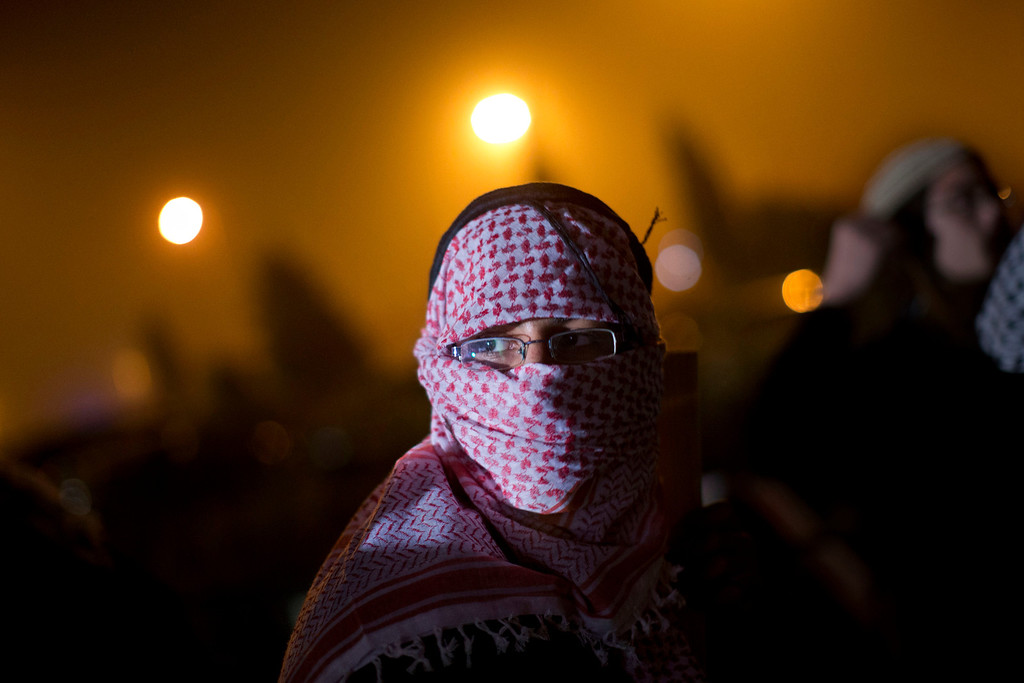 . An Israeli man with a keffiyeh, a traditional checkered head scarf, protests against the release of Palestinian prisoners from Israeli jails, outside the Ofer military prison near the West Bank city of Ramallah, Tuesday, Oct. 29, 2013. Dozenso of Israeli protesters demonstrated outside the West Bank prison where the inmates were held ahead of the release. (AP Photo/Bernat Armangue)
