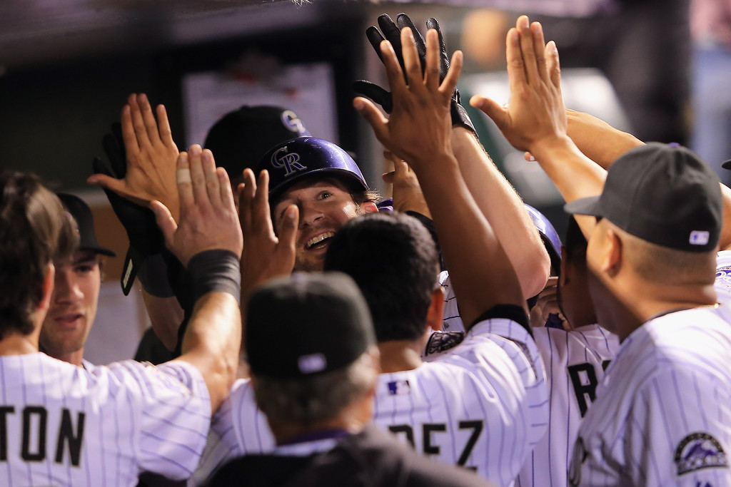 . DENVER, CO - AUGUST 10:  Charlie Blackmon #19 of the Colorado Rockies celebrates in the dugout after scoring on a single by Dexter Fowler #24 of the Colorado Rockies to take a 5-3 lead over the Pittsburgh Pirates in the sixth inning at Coors Field on August 10, 2013 in Denver, Colorado.  (Photo by Doug Pensinger/Getty Images)