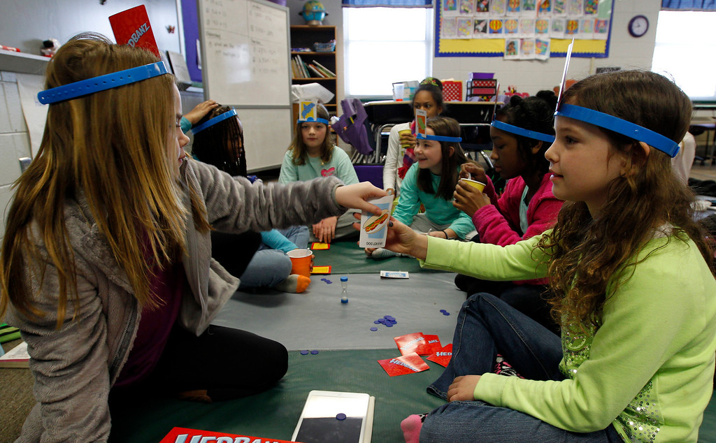 . Sydney Jaffe, left,  and Peyton Meadors, right,  play a card game with others students stranded at Oak Mountain Intermediate school on Wednesday, Jan. 29, 2014, in Indian Springs, Ala. (AP Photo/Butch Dill)