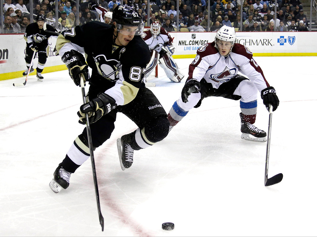 . Pittsburgh Penguins\' Sidney Crosby (87) works the puck in the corner against Colorado Avalanche\'s Nathan MacKinnon (29) in the second period of an NHL hockey game in Pittsburgh Monday, Oct. 21, 2013. (AP Photo/Gene J. Puskar)