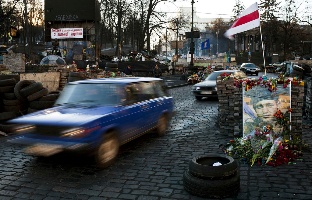 . Cars make their way past barricades placed on a road near the Dynamo Kyiv soccer club stadium in Kiev, Ukraine, Wednesday, March 12, 2014. (AP Photo/David Azia)