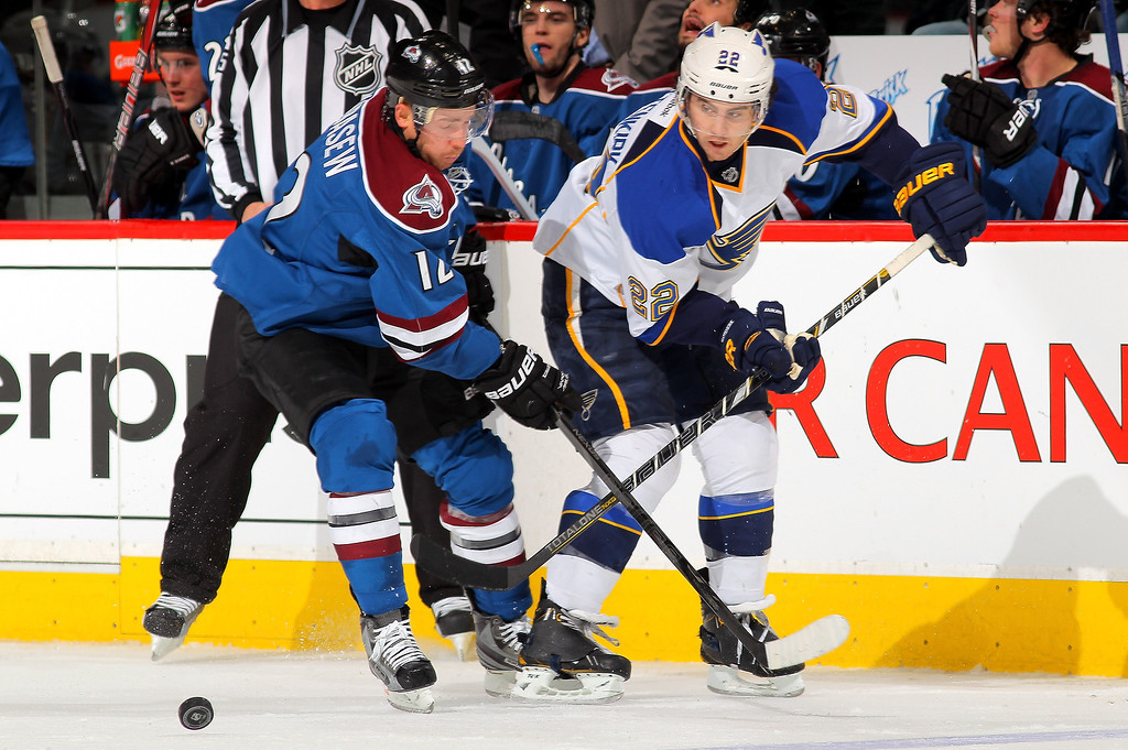 . Chuck Kobasew #12 of the Colorado Avalanche and Kevin Shattenkirk #22 of the St. Louis Blues battle for control of the puck at the Pepsi Center on February 20, 2013 in Denver, Colorado.  (Photo by Doug Pensinger/Getty Images)