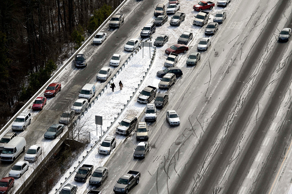 . In this aerial view looking at I-75 north at Mt. Paran Rd., abandoned cars are piled up on the median of the ice-covered interstate after a winter snow storm Wednesday, Jan. 29, 2014, in Atlanta.   (AP Photo/David Tulis)