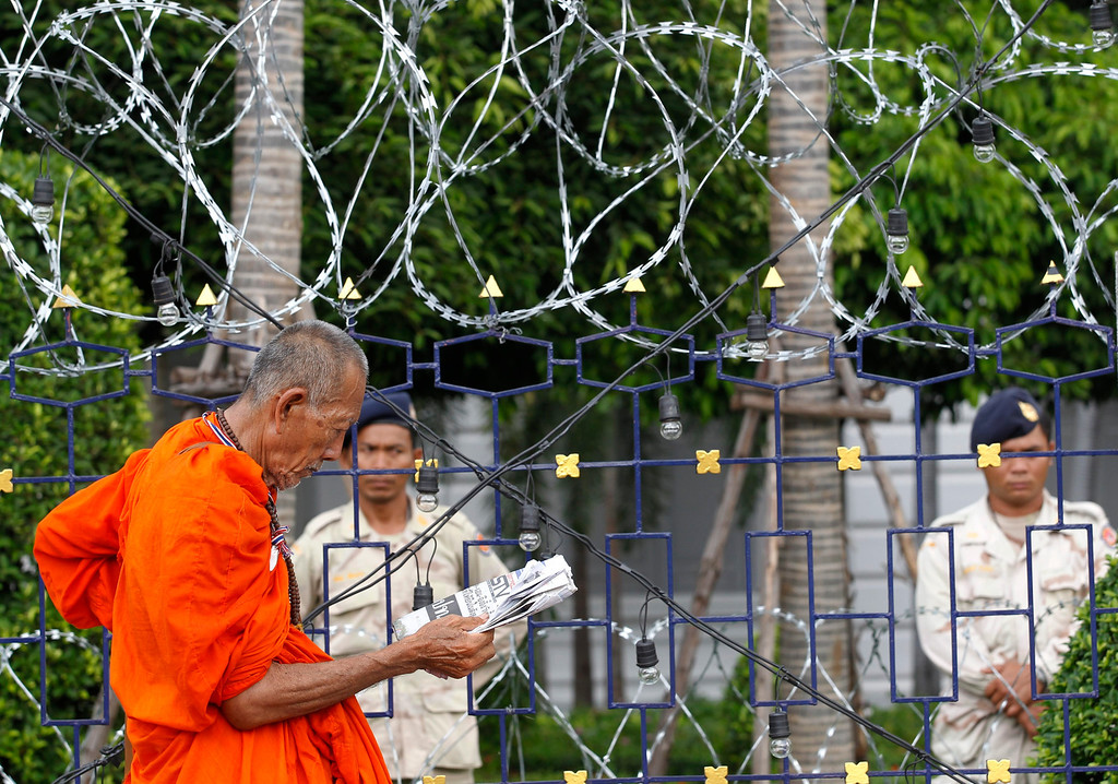 . A Thai Buddhist monk reads a newspaper as security personnel stand on duty during an anti-government protesters rally occupying the Interior Ministry in Bangkok, Thailand, 26 November 2013.   EPA/RUNGROJ YONGRIT