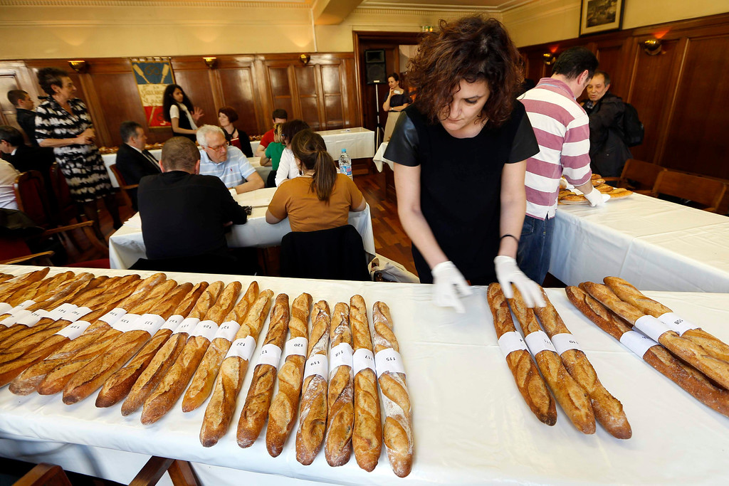 . Jury members taste and select baguettes in competition for the \'Grand Prix de la Baguette de la Ville de Paris\' (Best Baguette of Paris 2013) annual prize at the Chambre Professionnelle des Artisans Boulangers Patissiers in Paris April 25, 2013. The baguette is a French cultural symbol par excellence and the competition saw 203 Parisian bakers who compete for recognition as finest purveyor of one of France\'s most iconic staples. The baguettes are registered, given anonymous white wrappings and an identification number. They are then carefully weighed and measured to ensure they do not violate the contest\'s strict rules. 52 entries were withdrawn for failing to measure between 55-70cm long or not matching the acceptable weight of between 250-300g. Every year, the winner earns the privilege of baking bread for the French President.   REUTERS/Charles Platiau