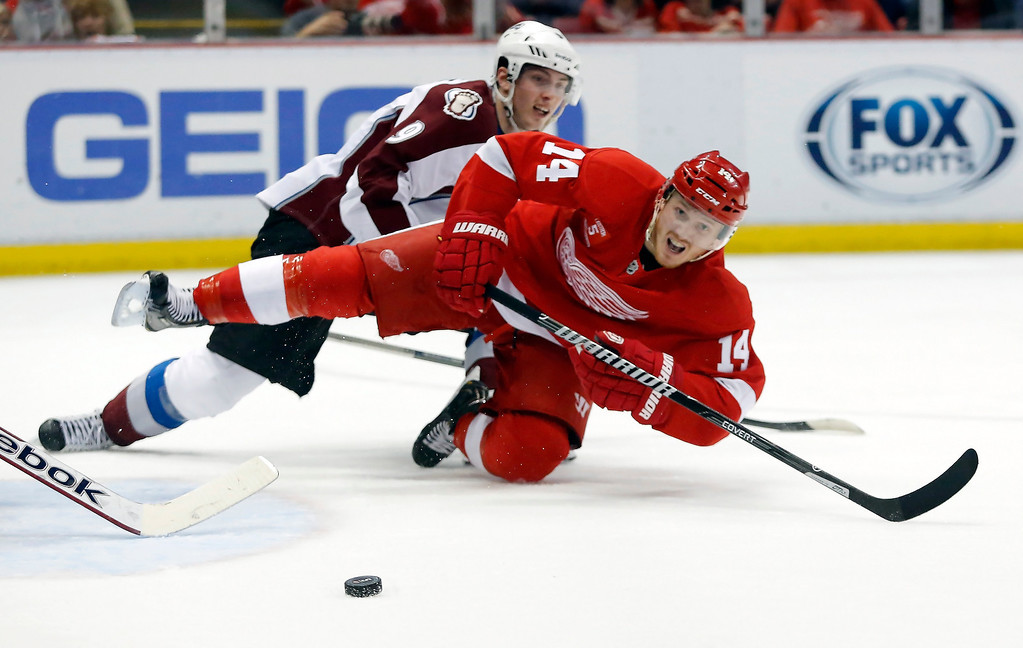 . Detroit Red Wings\' Gustav Nyquist (14), of Sweden, is knocked off his feet by Colorado Avalanche\'s Matt Duchene while trying to take a shot during the second period of an NHL hockey game Thursday, March 6, 2014, in Detroit. (AP Photo/Duane Burleson)
