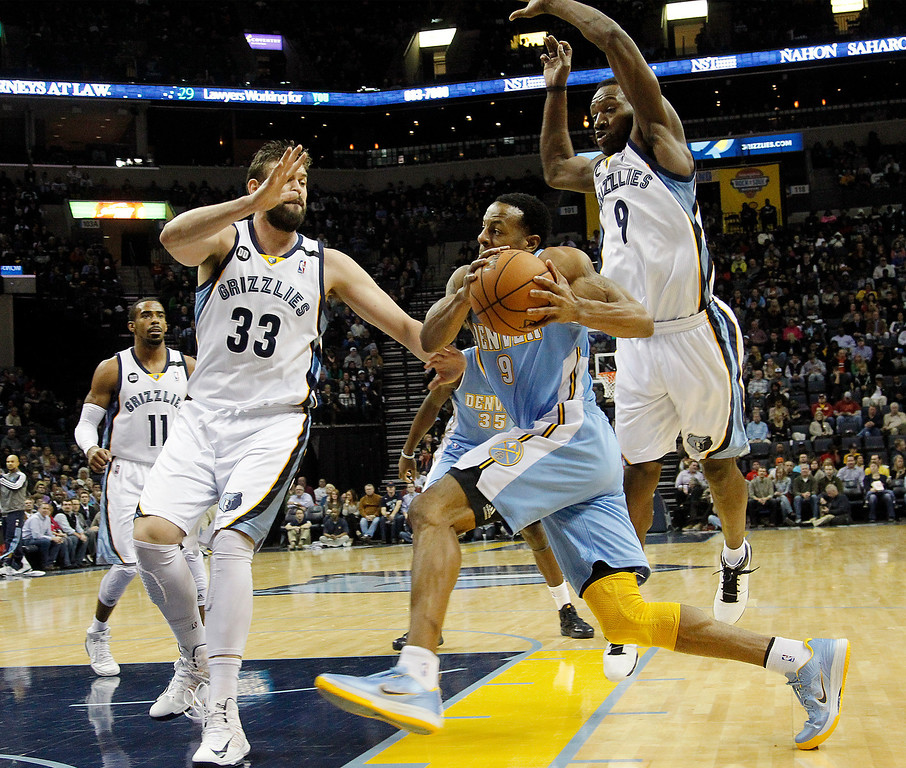 . Denver Nuggets guard Andre Iguodala, center, drives to the basket against Memphis Grizzlies defenders Marc Gasol (33), of Spain, and Tony Allen, right, in the first half of an NBA basketball game on Saturday, Dec. 29, 2012, in Memphis, Tenn. (AP Photo/Lance Murphey)