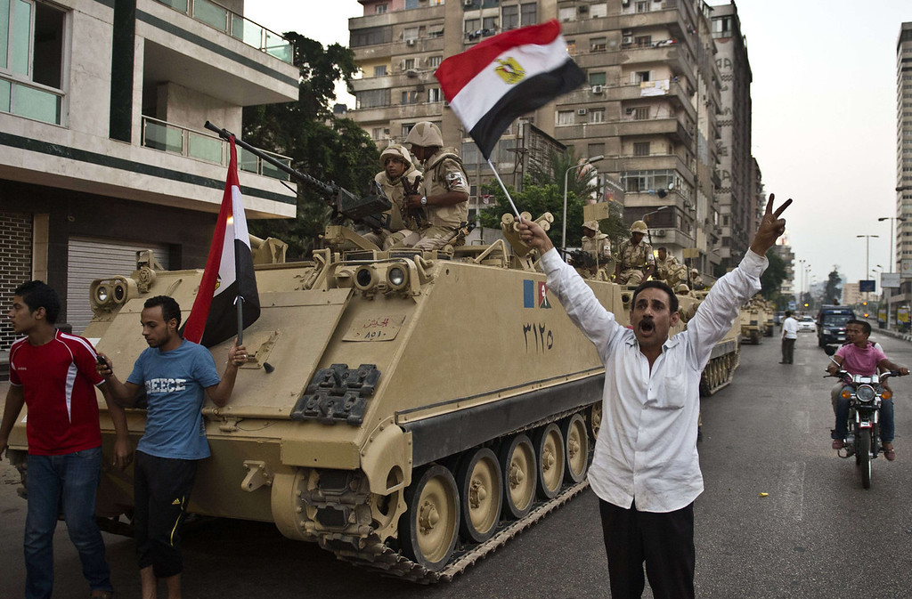 """. Egyptians salute Army tanks upon their deployment on a street leading to Cairo University on July 3, 2013. A top aide to Egypt\'s President Mohamed Morsi slammed what he called a \""""military coup\"""" as an army ultimatum passed and the security forces slapped a travel ban on the Islamist leader.  KHALED DESOUKI/AFP/Getty Images"""