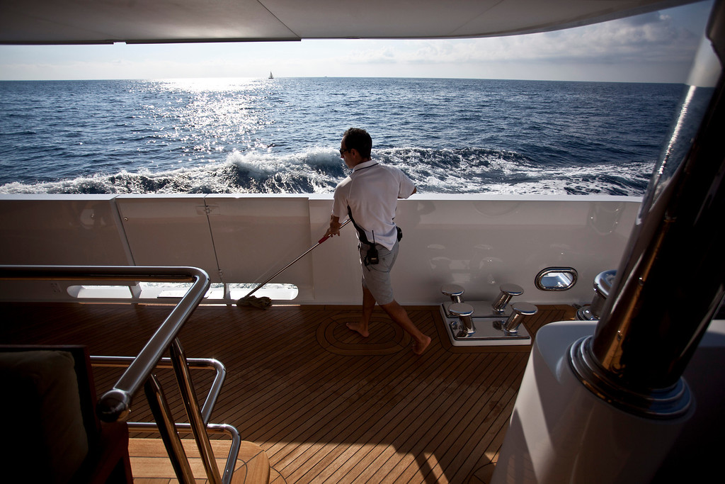 . A crew member cleans with a mop onboard the 190ft (57.9m) motor yacht Mi Sueno, manufactured by Trinity Yachts LLC, in the harbor in Nice, France, on Wednesday, Sept. 25, 2013.  Photographer: Balint Porneczi/Bloomberg