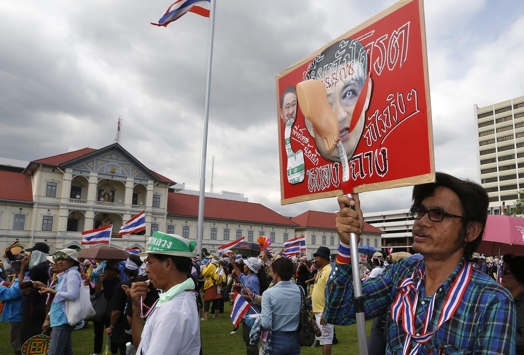 . A Thai anti-government protester holds a banner with the face of ousted former Prime Minister Thaksin Shinawatra with the insult of a foot stamped on his face, as protesters occupied the Royal Thai Army Headquarters (seen in background) in Bangkok, Thailand, 29 November 2013.   EPA/BARBARA WALTON