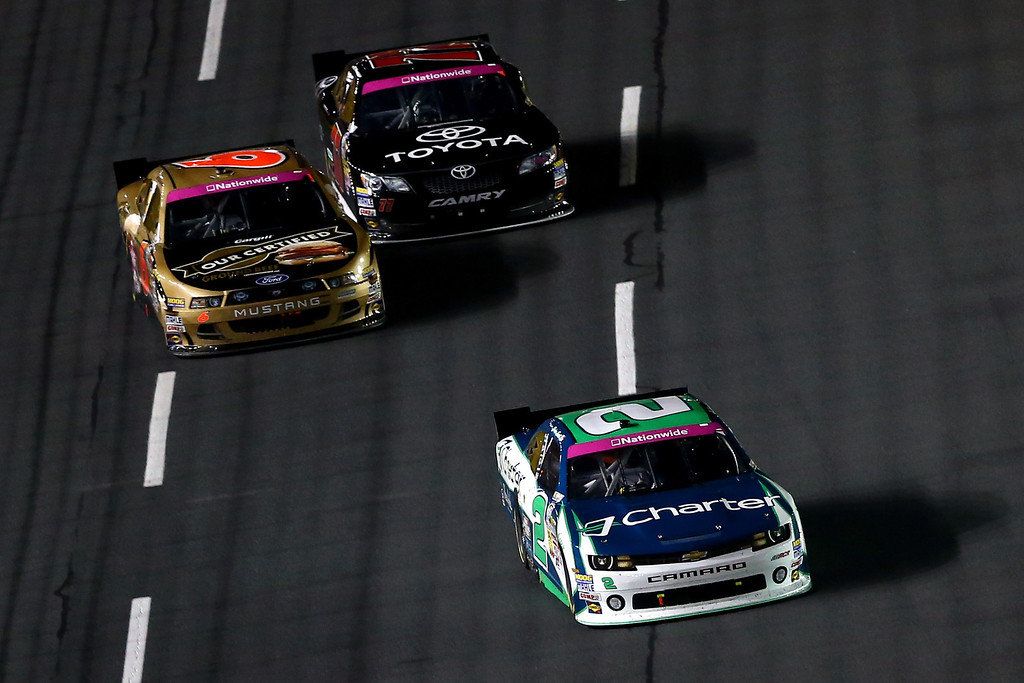 . CONCORD, NC - OCTOBER 11:  Brian Scott, driver of the #2 Charter Chevrolet, leads Trevor Bayne, driver of the #6 Cargill Ford, and Parker Kligerman, driver of the #77 TOYOTA Toyota, during the NASCAR Nationwide Series Dollar General 300 at Charlotte Motor Speedway on October 11, 2013 in Concord, North Carolina.  (Photo by Streeter Lecka/Getty Images)