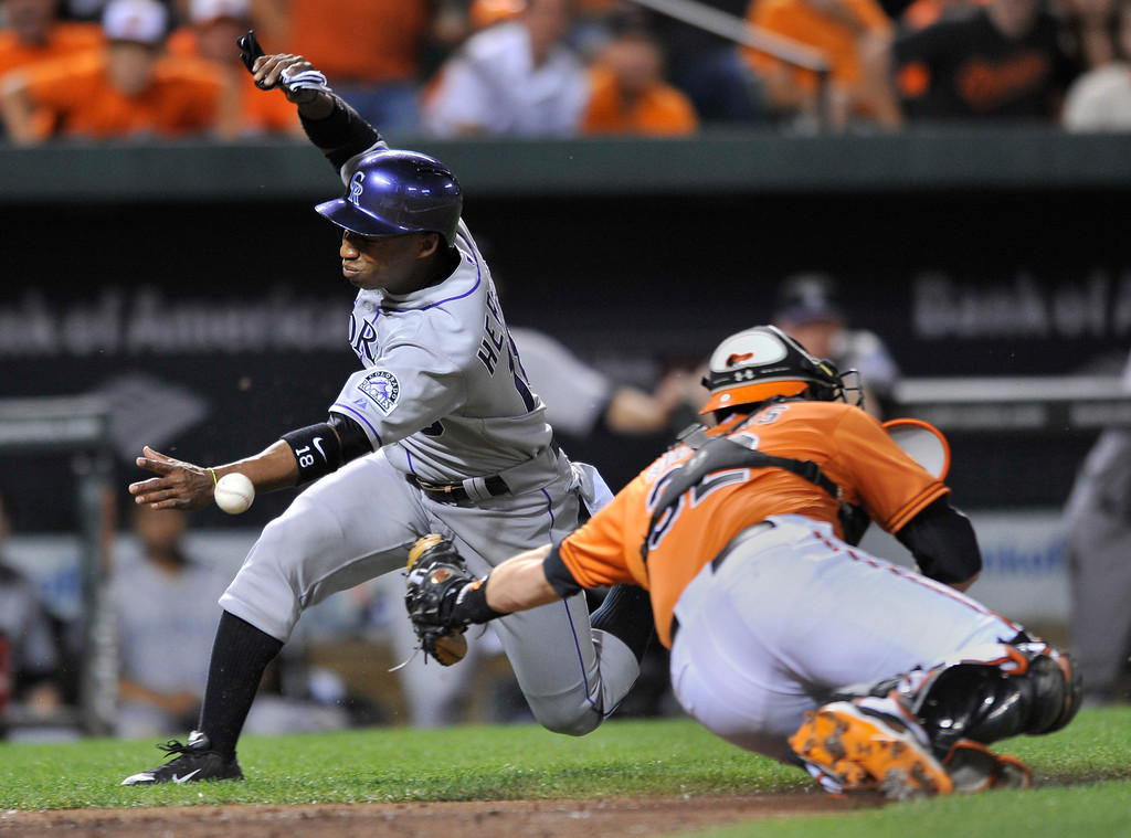 . Baltimore Orioles catcher Matt Wieters, right, reaches for Colorado Rockies Jonathan Herrera who slides into home on a double by Dexter Fowler in the sixth inning of a baseball game on Saturday, Aug. 17, 2013, in Baltimore. Herrera was safe on the play. (AP Photo/Gail Burton)