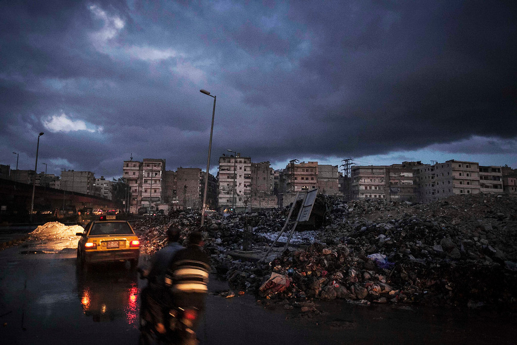 . FILE - Motorists drive past damaged buildings in Aleppo, Syria, Tuesday, Dec. 4, 2012. (AP Photo/Narciso Contreras, File)