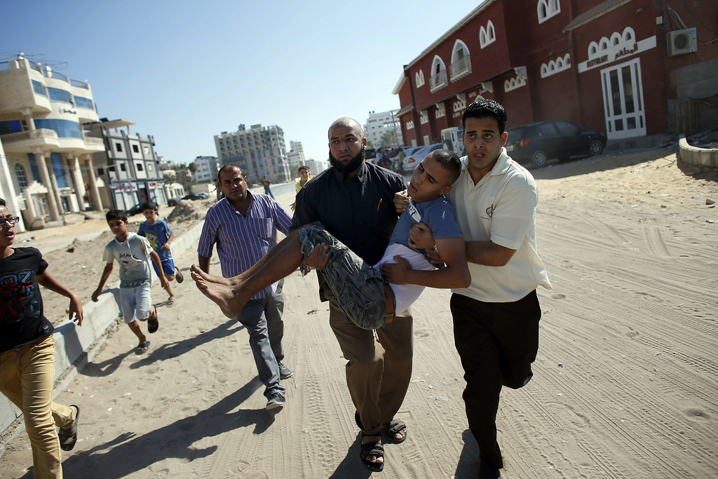 . Palestinian employees of Gaza City\'s al-Deira hotel carry a wounded boy following an Israeli military strike nearby on the beach, on July 16, 2014. Four children were killed in Gaza City during the attack, medics said, in Israeli shelling witnessed by AFP journalists. All four were on the beach when the attack took place, emergency services spokesman Ashraf al-Qudra said, with several injured children taking refuge at a nearby hotel where journalists were staying. AFP PHOTO / THOMAS  COEX/AFP/Getty Images