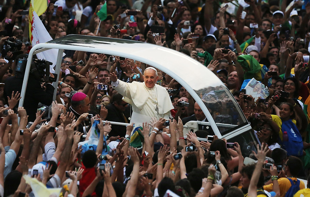 . Pope Francis waves to the crowd while departing the Metropolitan Cathedral in the Popemobile after arriving in Rio on July 22, 2013 in Rio de Janeiro, Brazil.  (Photo by Mario Tama/Getty Images)
