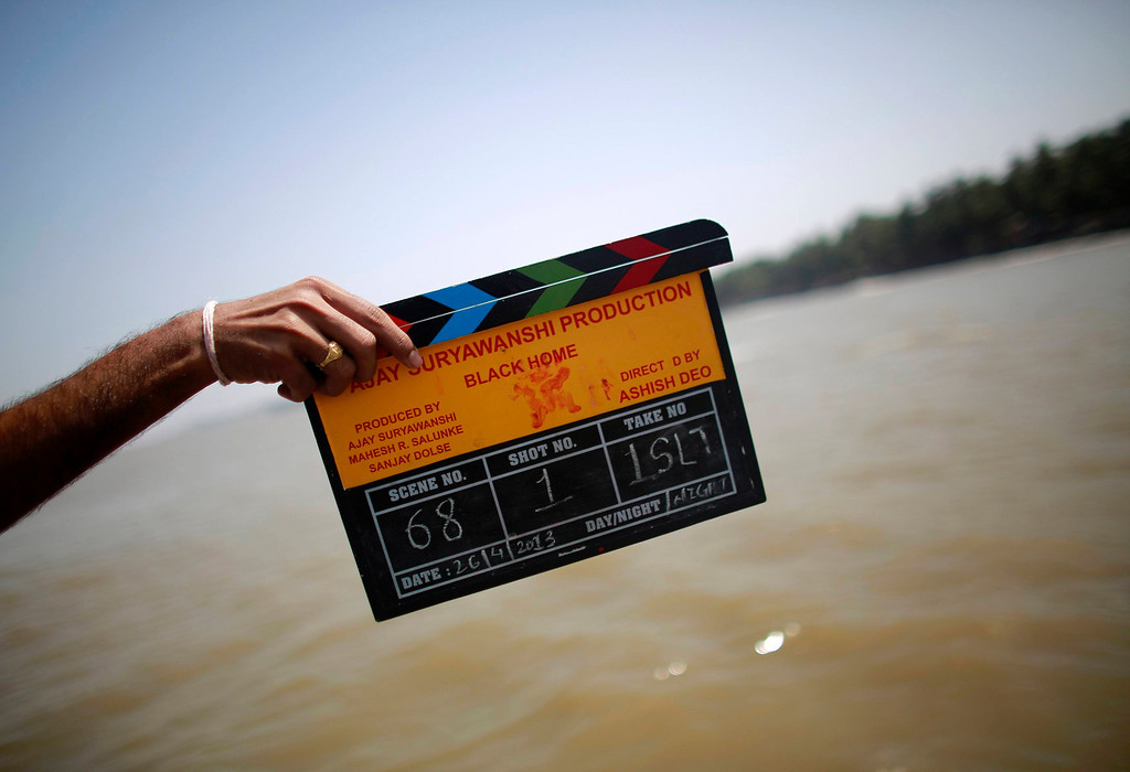 ". A member of a film crew holds a clapper board during the shooting of Bollywood film \'Black Home\' at a beach on the outskirts of Mumbai April 26, 2013. Indian cinema marks 100 years since Dhundiraj Govind Phalke\'s black-and-white silent film ""Raja Harishchandra\"" (King Harishchandra) held audiences spellbound at its first public screening on May 3, 1913, in Mumbai. Indian cinema, with its subset of Bollywood for Hindi-language films, is now a billion-dollar industry that makes more than a thousand films a year in several languages. It is worth 112.4 billion rupees (over $2 billion) and leads the world in terms of films produced and tickets sold. Picture taken April 26, 2013. REUTERS/Danish Siddiqui"