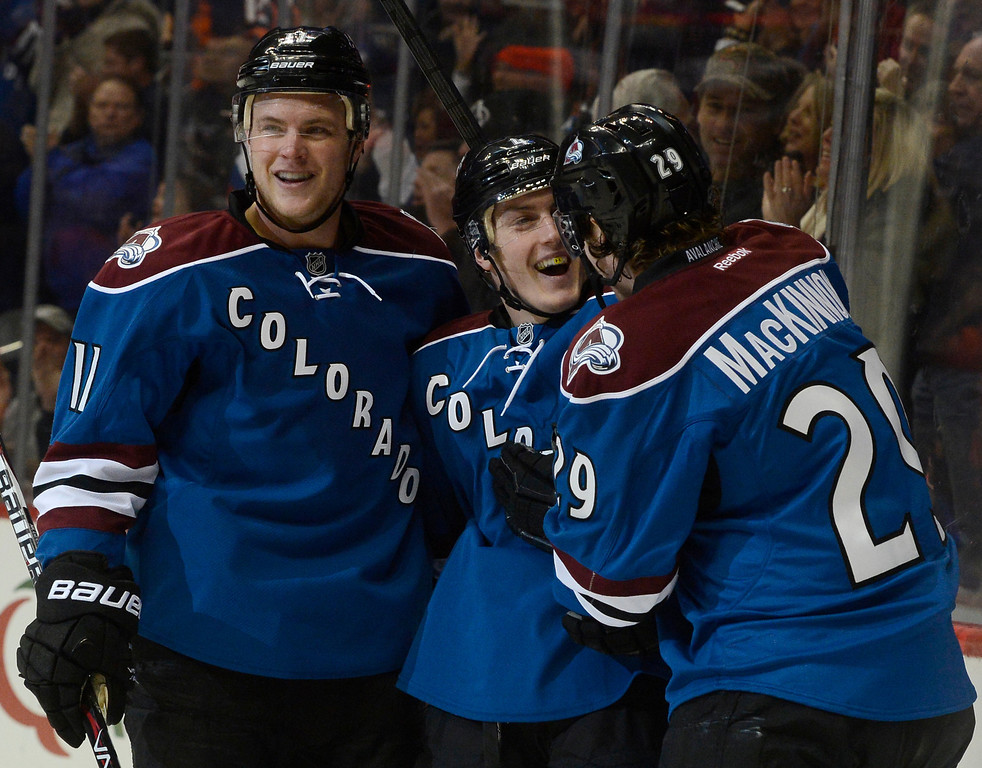 . Colorado Avalanche defenseman, Tyson Barrie, center, celebrates his first period goal against the Buffalo Sabres with teammates, Nathan MacKinnon, right, who got the assist, and Jamie McGinn, left, Saturday afternoon, February 01, 2014. The Avalanche won 7-1. (Photo By Andy Cross / The Denver Post)