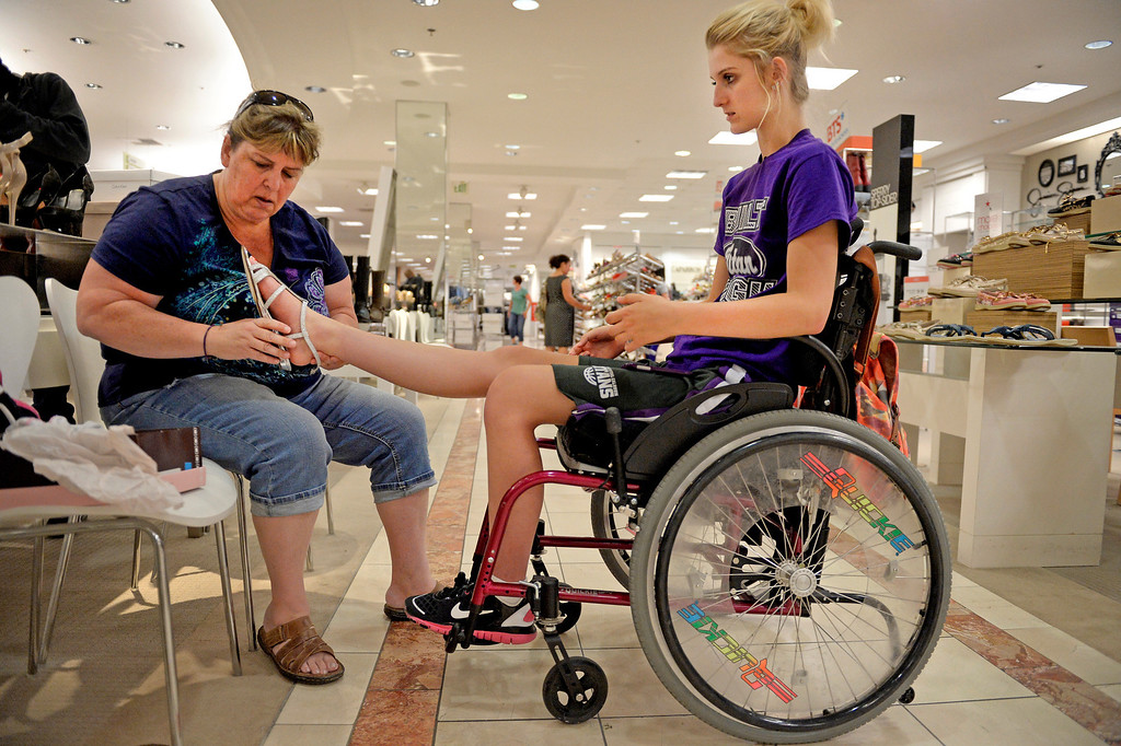 . Mackenzie and her mother, Karen, do some shoe shopping at Cherry Creek Mall during a break from physical therapy in early August. Mackenzie was looking for the wedding shoes she hoped to wear in September. (Photo By Craig F. Walker / The Denver Post)