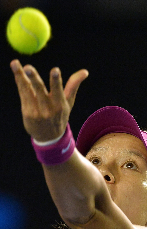 . Li Na of China serves against Dominika Cibulkova of Slovakia during the women\'s singles final on day 13 of the 2014 Australian Open tennis tournament in Melbourne on January 25, 2014. (PAUL CROCK/AFP/Getty Images)