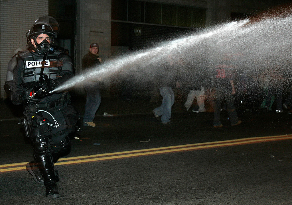 . A policeman in riot gear disperses the crowd with pepper spray outside Fenway Park in Boston as they celebrate after the Red Sox beat the St. Louis Cardinals to win the World Series Wednesday, Oct. 27, 2004. . (AP  Photo/Michael Dwyer)