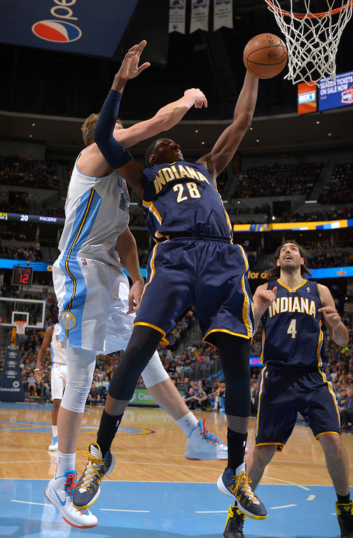 . Indiana Pacers center Ian Mahinmi (28) from France grabs a rebound from Denver Nuggets center Timofey Mozgov (25) from Russia during the second quarter of an NBA basketball game Saturday, Jan. 25, 2014, in Denver. (AP Photo/Jack Dempsey)