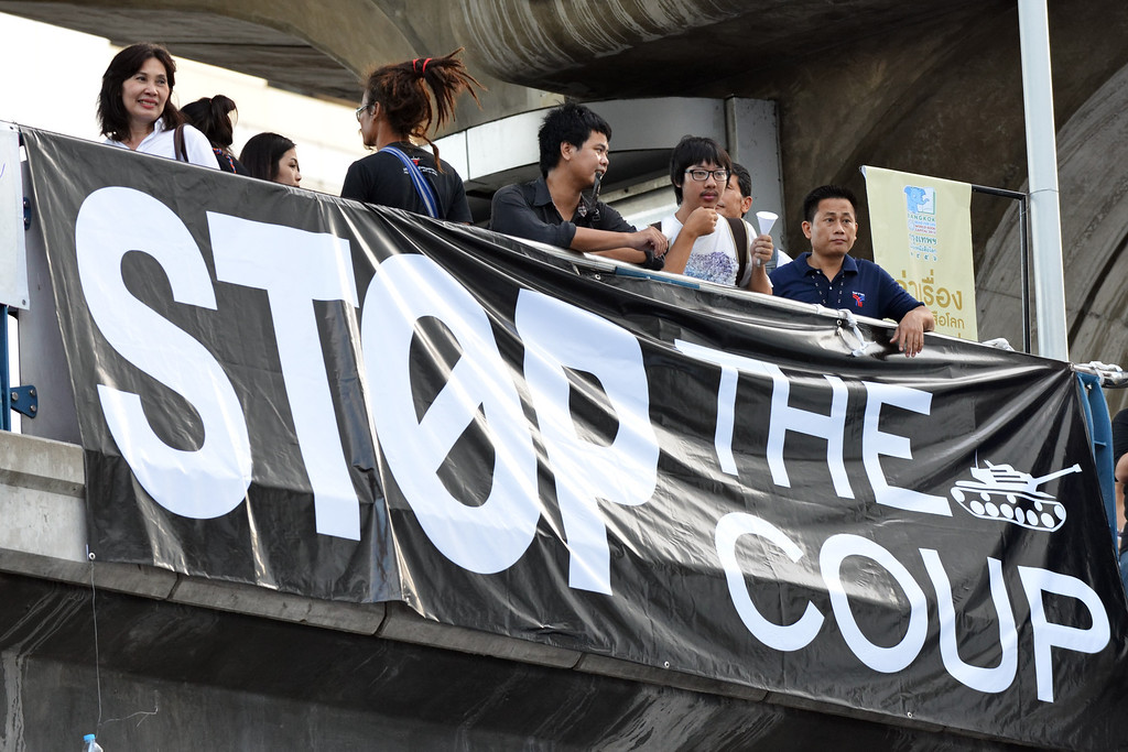. Protesters gather by a large banner during an anti-coup rally on May 23, 2014 in Bangkok, Thailand. Anti-coup protesters rallied in Bangkok\'s shopping district, a day after the military seized control in a bloodless coup. (Photo by Rufus Cox/Getty Images)