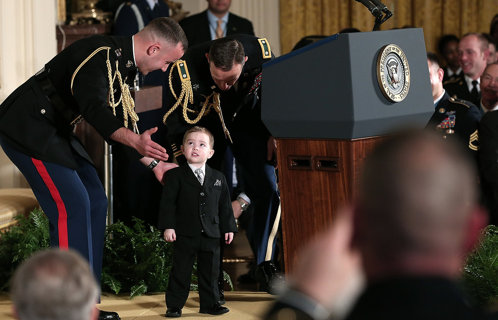 . White House military aides corral Colin Romesha, the son of Medal of Honor recipient Clinton Romesha, after he took the stage behind U.S. President Barack Obama\'s lectern before a presentation ceremony at the White House February 11, 2013 in Washington, DC. (Photo by Win McNamee/Getty Images)