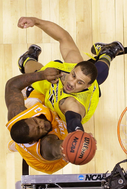 . Michigan\'s Jordan Morgan, right, blocks a shot by Tennessee\'s Jeronne Maymon during the second half of an NCAA Midwest Regional semifinal college basketball tournament game Friday, March 28, 2014, in Indianapolis. (AP Photo/Michael Conroy)