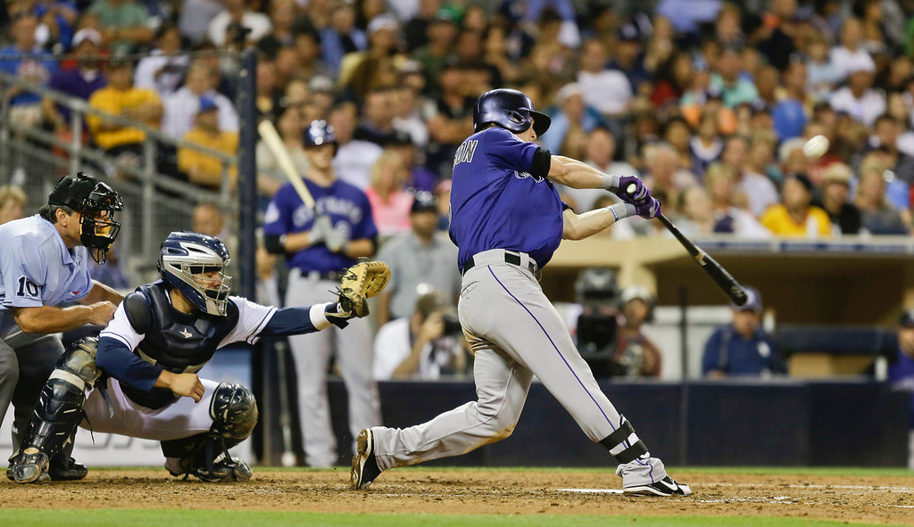. Colorado Rockies\' Corey Dickerson lofts a deep sacrifice fly to bring in a run against the San Diego Padres in the sixth inning of a baseball game in San Diego, Monday, July 8, 2013. (AP Photo/Lenny Ignelzi)