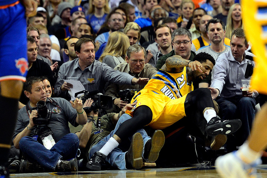 . DENVER, CO - MARCH 13: Wilson Chandler (21) of the Denver Nuggets falls on a photographer during the first half of action. The Denver Nuggets play the New York Knicks at the Pepsi Center. (Photo by AAron Ontiveroz/The Denver Post)