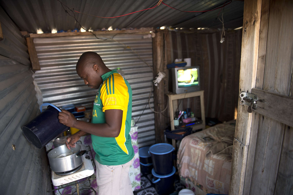 . A miner prepares food in his shack on July 9, 2013 in the Nkaneng shantytown next to the platinum mine, run by British company Lonmin, in Marikana. On August 16, 2012, police at the Marikana mine open fire on striking workers, killing 34 and injuring 78, during a strike was for better wages and living conditions. Miners still live in dire conditions despite a small wage increase.  ODD ANDERSEN/AFP/Getty Images