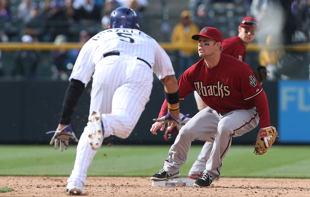 . Arizona Diamondbacks second baseman Aaron Hill, back, waits for throw as Colorado Rockies\' Carlos Gonzalez steals second base in the ninth inning of the Diamondbacks\' 5-3 victory in a baseball game in Denver on Sunday, April 6, 2014. (AP Photo/David Zalubowski)