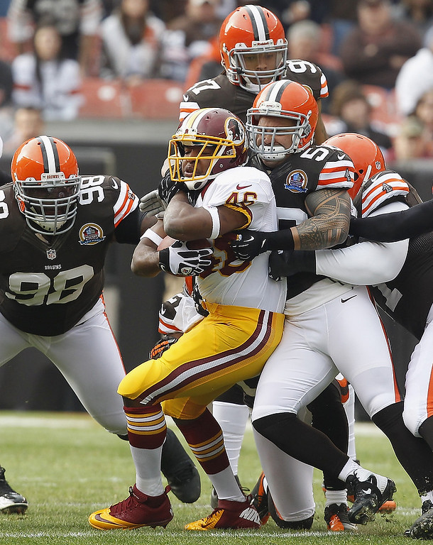 . Running back Alfred Morris #46 of the Washington Redskins is hit by defenders Kaluka Maiava #56, Phil Taylor #98 and Jabaal Sheard #97 of the Cleveland Browns at Cleveland Browns Stadium on December 16, 2012 in Cleveland, Ohio.  (Photo by Matt Sullivan/Getty Images)