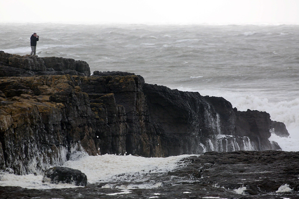 . A man stands on the rocky coastline as waves roll in in Porthcawl, south Wales on October 27, 2013 ahead of the arrival of a predicted storm. Britain was braced on October 27 for its worst storm in a decade, with heavy rain and winds of more than 80 miles (130 kilometres) an hour set to batter the south of the country.   GEOFF CADDICK/AFP/Getty Images