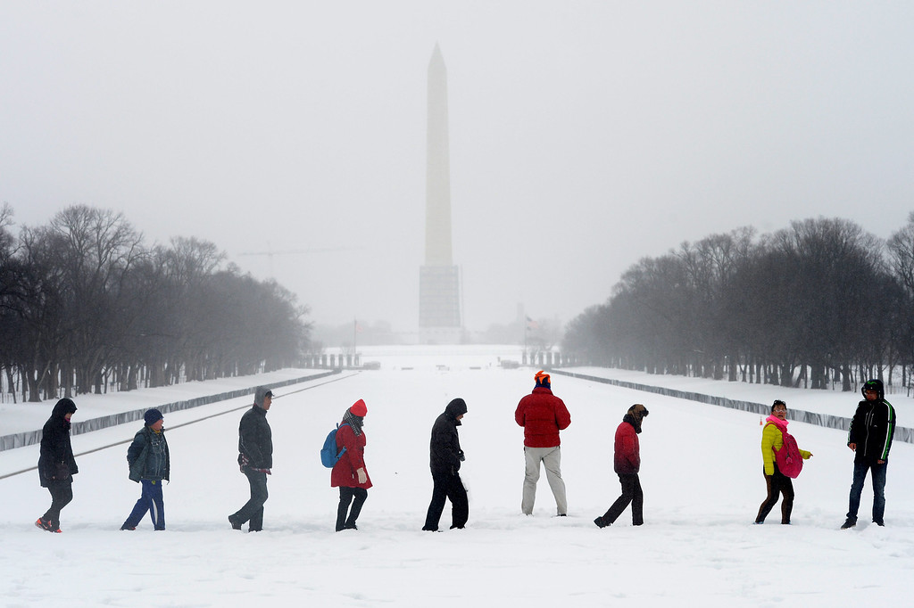 . The Washington Monument (back) is barely visible behind visitors to the Lincoln Memorial  in Washington DC, USA, 13 February 2014. The Washington DC area was pounded by a snowstorm, with accumulation expected to reach twelve inches in some areas, as the storm moved up the mid-Atlantic to the Northeast region of the US.  EPA/MICHAEL REYNOLDS